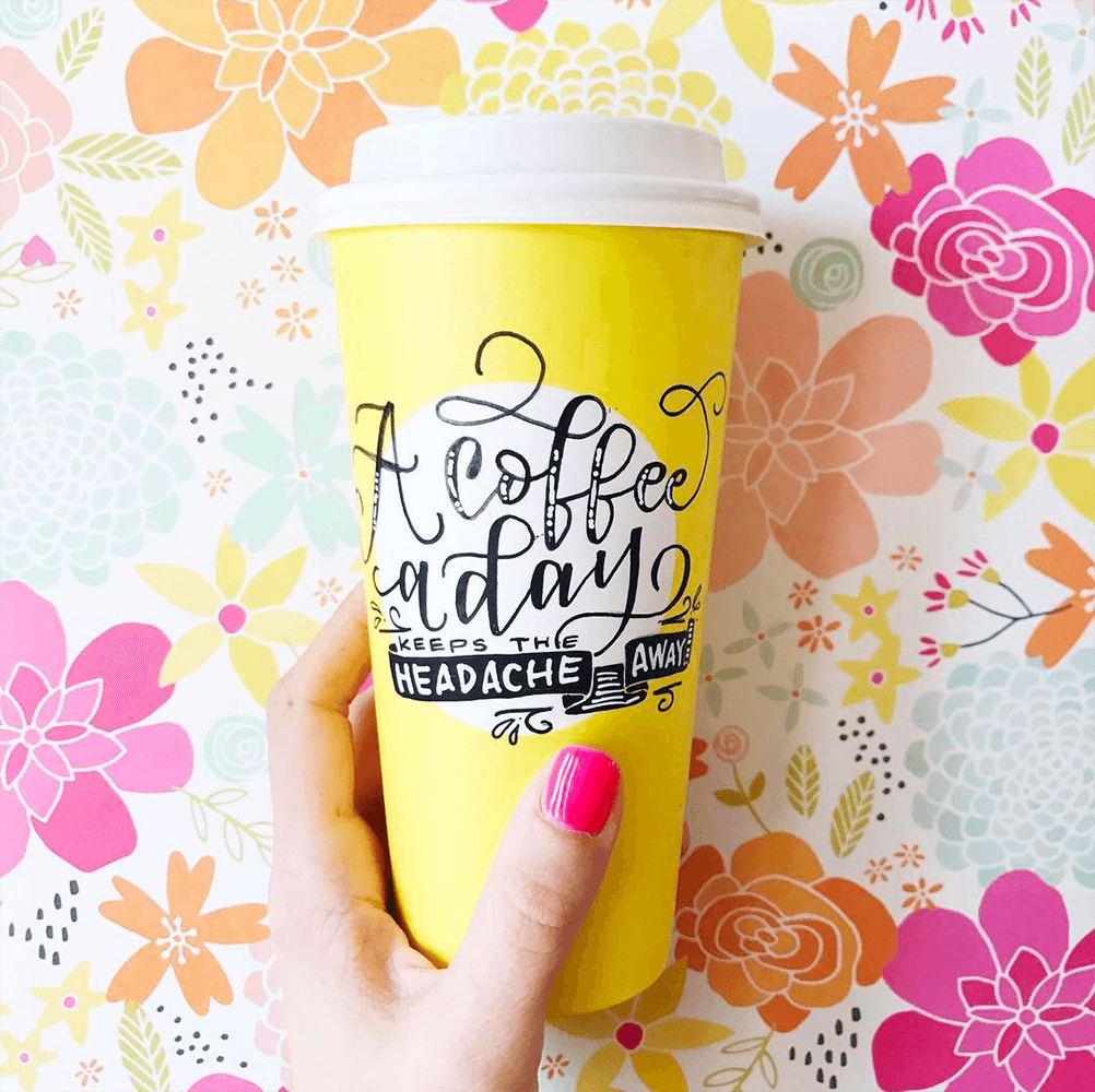 Yellow hand lettered coffee cup with flower background