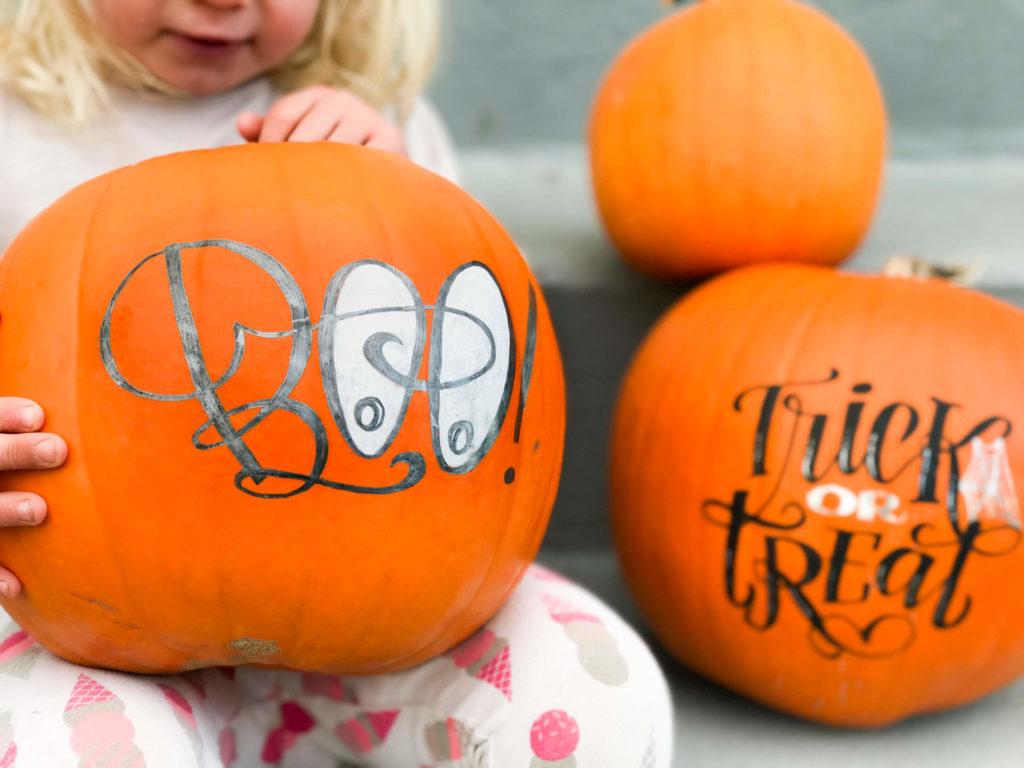 Little girl holding hand lettered pumpkin